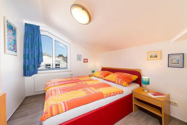 Das Schlafzimmer mit gemütlicher Dachschräge und Doppelbett sowie Gardine und Plissee am Fenster.