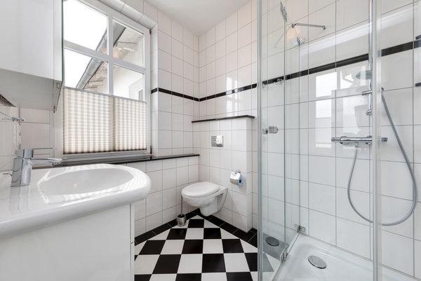 Das Bad bietet Ihnen Echtglasdusche, WC und Fenster mit Plissee.