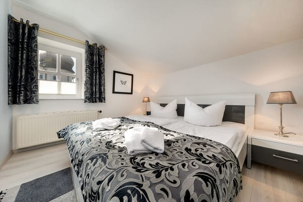 Das Schlafzimmer (mit Dachschräge) hat ein Doppelbett und einen kleinen Kleiderschrank.