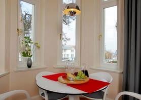 Große Fenster sorgen für besondere Lichtspiele, insbesondere in dem am Wohnbereich angrenzend traumhaften Erker, der mit einem gemütlichen Esstisch aufwartet.
