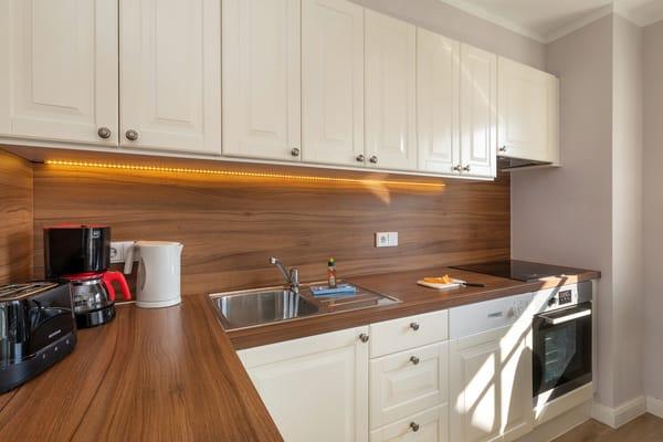 Die komplett mit Geschirrspüler, Backofen, Geschirr etc. ausgestattete Küchenzeile.