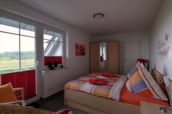 Geräumiges Schlafzimmer mit Doppelbett und Balkon