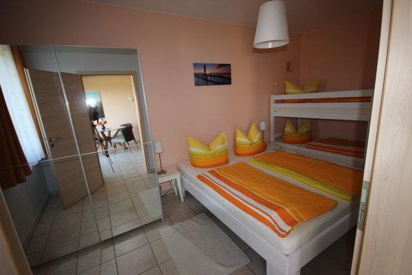 Im Schlafzimmer befinden sich ein Doppel- und ein Etagenbett. Das Kinderbettchen hat auch noch Platz.