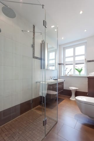 ... mit einer ebenerdigen Echtglas-Dusche, WC und einem Haarfön ausgestattet.  Waschmaschine und Trockner im Haus sind gegen eine Gebühr nutzbar.