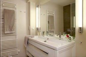 Das Badezimmer ist mit italienischem Feinsteinzeug, einem großen Waschtisch und einer bodengleichen Echtglasdusche ausgestattet.