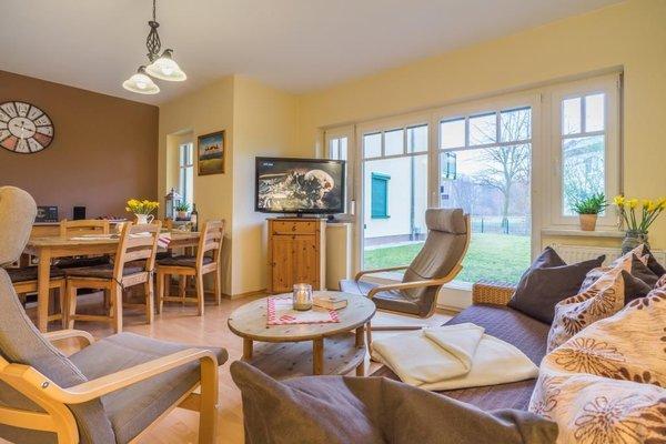 Wohnbereich mit Esstisch, Sofa, Flat TV, DVD Player und Zugang zur Terrasse, welche zur Tagessonne ausgerichtet ist.