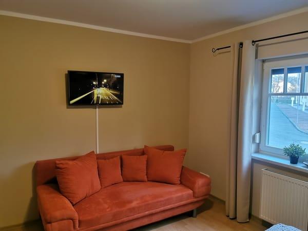 ist mit Doppelbett, Kleiderschrank und zusätzlichem Sofa ausgestattet und Flat TV an der Wand angebracht.