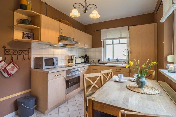 Eine vollausgestattete Küche mit Ceranfeld, Geschirrspüller, Kühlschrank mit Gefrierfach und vielen anderen Küchengeräten.