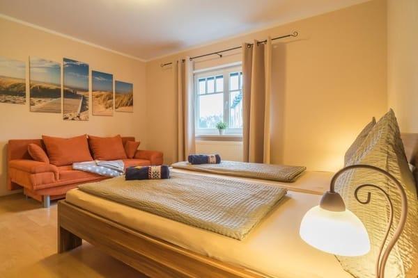 Schlafzimmer ist mit Doppelbett, Kleiderschrank und zusätzlichem Sofa ausgestattet und Flat TV an der Wand angebracht.