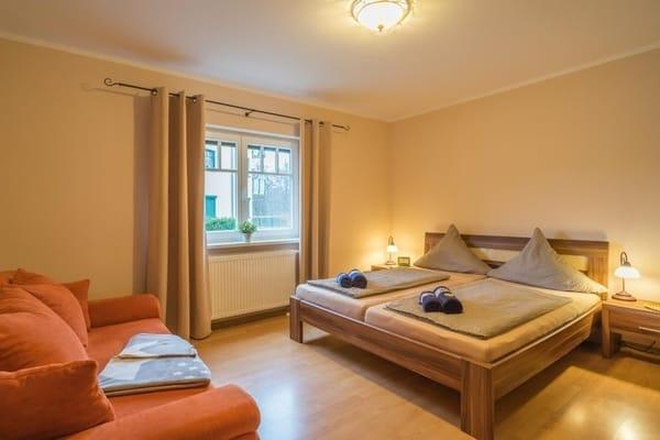 Schlafzimmer ist mit Doppelbett, Kleiderschrank und zusätzlichem Sofa ausgestattet.