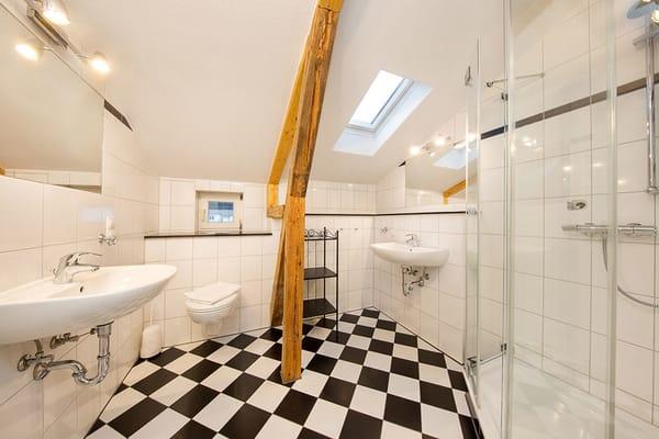 Das neue Bad hat 2 Waschbecken, Echtglasdusche und WC. Das Bad hat ebenfalls eine Dachschräge.