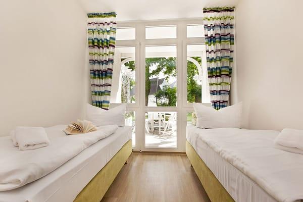 Im zweiten Schlafzimmer befinden sich zwei Boxspringbetten, die je nach Bedarf einzeln oder zusammen gestellt werden können. Kleiderschrank und Verdunkelungsgardinen sind ebenfalls vorhanden.