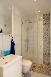 Ein weiteres Highlight ist das exklusive Badezimmer mit Echtglas-Dusche und bodengleicher Duschtasse.