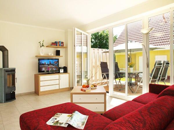 Wohnbereich mit Schlafcouch und Zugang zur Terrasse