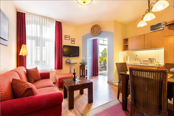 Die Wohnung ist in geschmackvollen Wohlfühlfarben eingerichtet. Von der Couch aus sehen Sie durch das Balkonfenster aufs Meer.