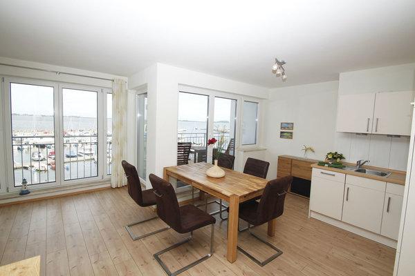 Koch-Essbereich mit Backofen und Geschirrspüler, daneben Balkon mit Panoramablick auf´s Wasser