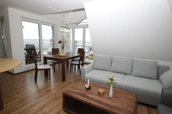 Wohnzimmer mit Balkon und Panoramablick auf die Hafenpromenade