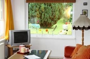 Wohnzimmer mit Nachmittagssonne und gemütlicher Sitzgruppe