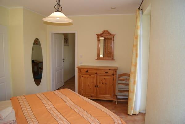 Schlafzimmer mit Doppelbett und Terrassenzugang.