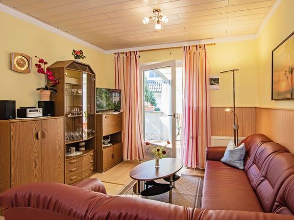 Wohnbereich mit TV, Couch und Blick auf die Terrasse.