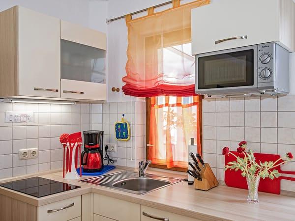 Küche mit Herd, Kaffeemaschine und Mikrowelle.