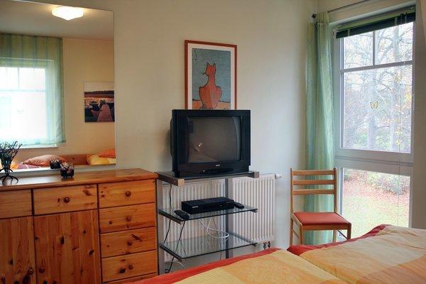 großes Schlafzimmer mit Gesundheitsmatratzen, großem Schrank, Spiegel und Fernseher, Blick in Park, Komode
