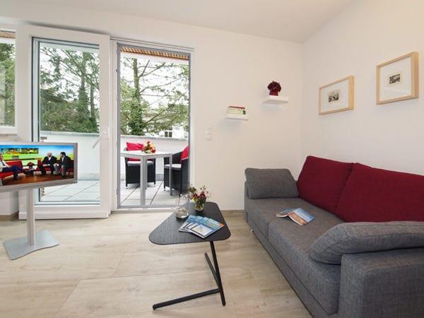 Wohnzimmer mit Sitzecke und Zugang zur Dachterrasse