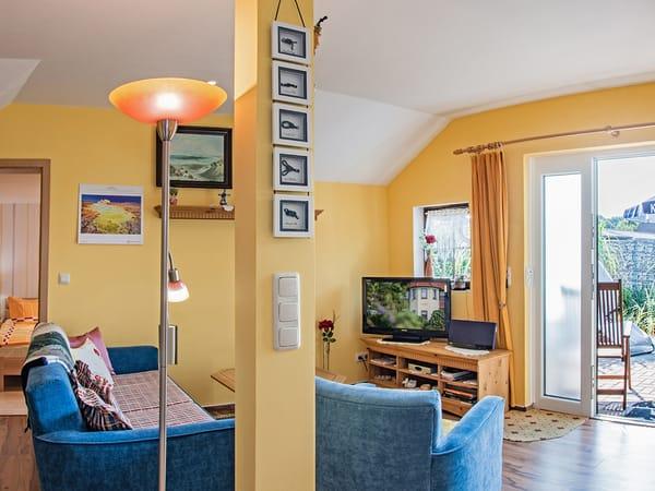 Wohnbereich mit Couch, TV und Blick auf die Terrasse.
