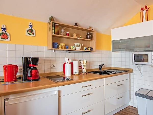Küche mit Kaffeemaschine, Wasserkocher und Toaster.