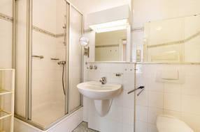 Das schöne Bad hat Dusche, WC und Waschbecken.