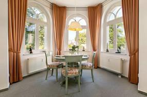 Im großen Erker des Wohnzimmers ist ein komfortabler Eßplatz eingerichtet.