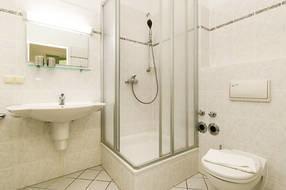 Das Bad hat Dusche, Waschbecken und WC.