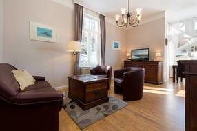 Das Wohnzimmer hat eine bequeme Couch mit Schlaffunktion und einen großen Flachbild-TV.