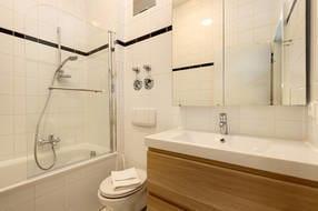 Im Badezimmer haben Sie eine Badewanne mit integrierter Dusche und Duschabtrennung, Waschtisch und WC.