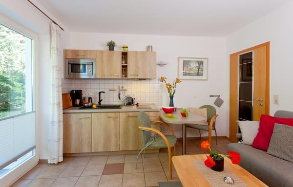 ... Kühlschrank mit Gefrierfach, Wasserkocher, Toaster, Kaffeemaschine und Eierkocher) sowie einem Esstisch für zwei Personen.