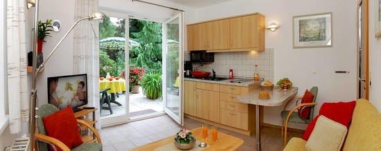 Der Wohnbereich verfügt über eine integrierte Küchenzeile mit Esstisch sowie über ein gemütliches Sofa, auf dem Sie nach einem erholsamen Urlaubstag die Seele baumeln lassen können.