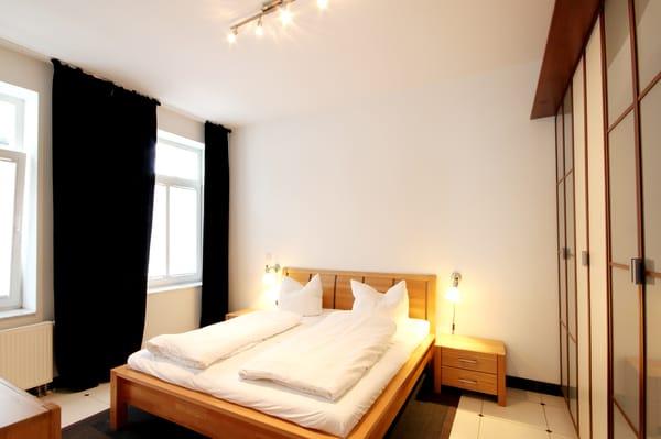 Schlafzimmer mit Doppelbett, großem Kleiderschrank und TV