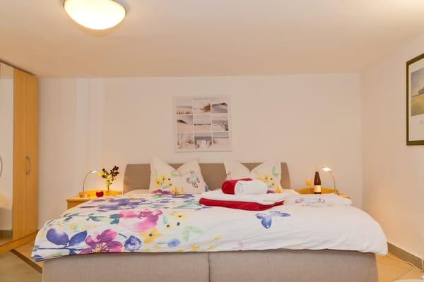 Warme mediterrane Farben schaffen in Wohn- und Schlafzimmer eine angenehme und gemütliche Atmosphäre. Das gemütliche Doppelbett (180x200cm) lockt für zur Nachtruhe.