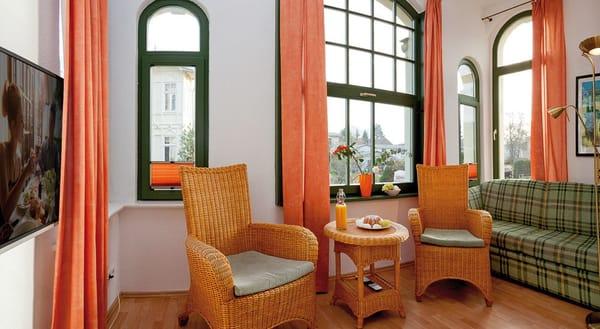 Das helle Drei-Zimmer-Appartement befindet sich im Hochparterre und besitzt eine Wohnfläche von 60 Quadratmetern. die Loggia lädt mit gemütlichen Polstermöbeln zum Entspannen und zu Spieleabenden ein.