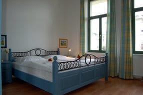 Im Schlafzimmer wartet ein bequemes Doppelbett auf Sie. Die Einrichtung ist in hellen Blautönen gehalten, so dass Sie sich zur Nachtruhe wie im Himmel fühlen.