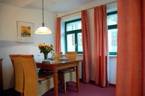 Der großzügige Wohnraum ist mit bequemen Polstermöbeln ausgestattet, die nach einem anstrengenden Tag zum entspannen einladen. Ein Esstisch bietet Platz für vier Personen.