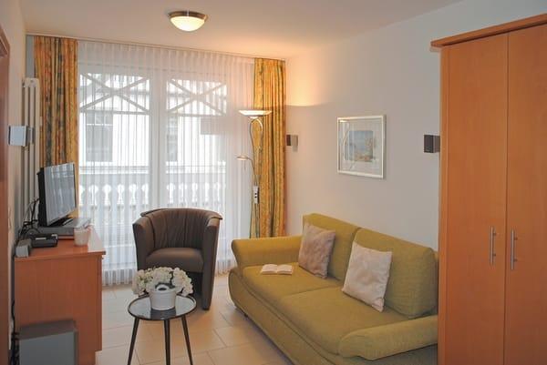 Wohnraum mit Couch, Sessel und TV