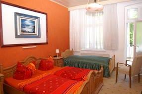 Schlafzimmer 1 mit einem Doppelbett  und einem Einzelbett ,Kleiderschrank, TV und Ausgang zum Balkon