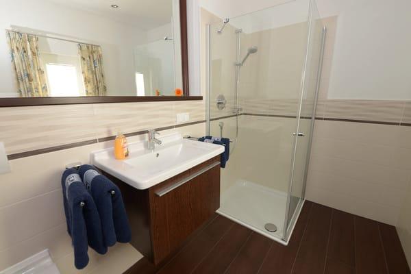 Das Badezimmer mit großzügiger Dusche und WC