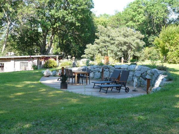 Große Terrasse im äußeren Gartenbereich mit Bestuhlung, Liegestühlen und Kunst