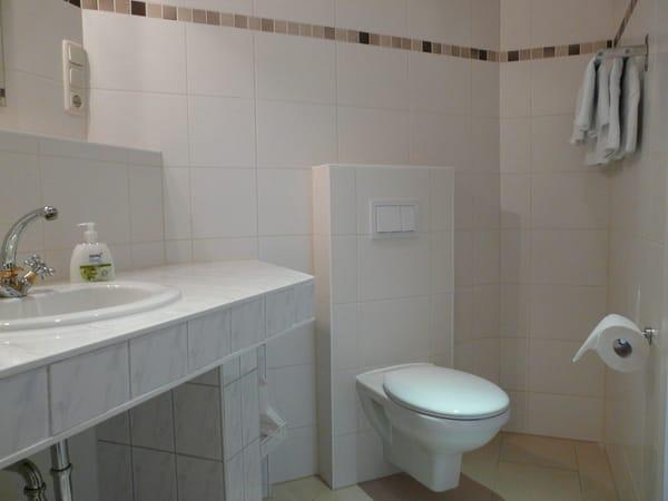Waschtisch und WC, ausreichend Ablageflächen und Handtuchhalter sind vorhanden
