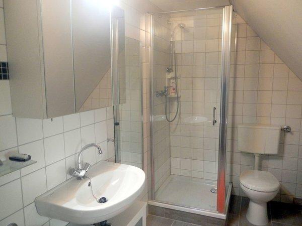 Das Badezimmer befindet sich unter dem Dach und ist über eine kleine Treppe zu erreichen.