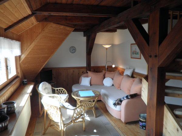 Gemütliches sonniges Wohnzimmer mit Treppe zum oberen Schlafraum.
