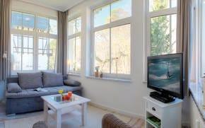 In dem Wintergarten - mit traumhaften Blick in den gegenüberliegenden Park und Flat-TV - des 29m² großen Appartements,bietet die hochwertige Couch perfekten Schlafkomfort (170x200cm) f. 2 Personen.