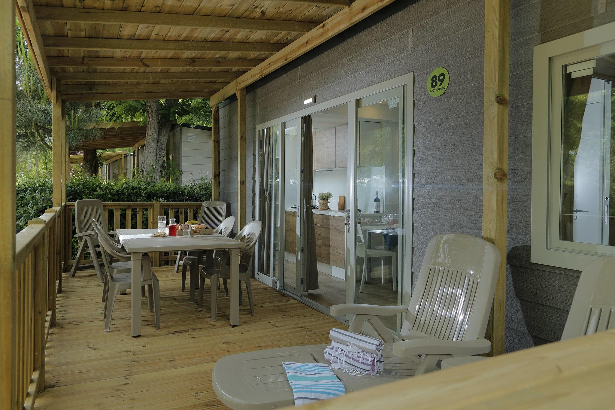 Veranda con sdraio e tavolo esterno nel verde